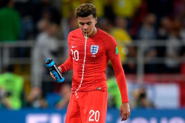 El inglés Delle Ali escupe el agua después de enjuagarse la boca con el líquido durante un partido en el Mundial de Rusia 2018.