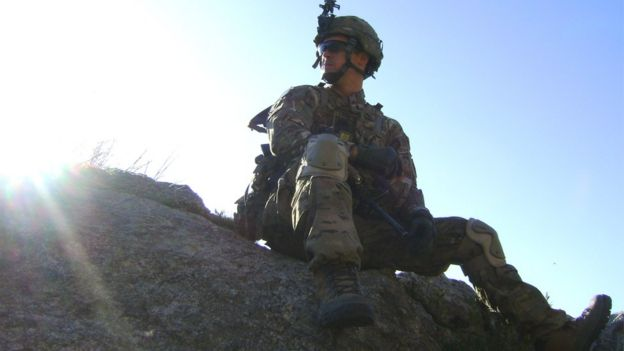 Joseph Laws in uniform sitting on a rock