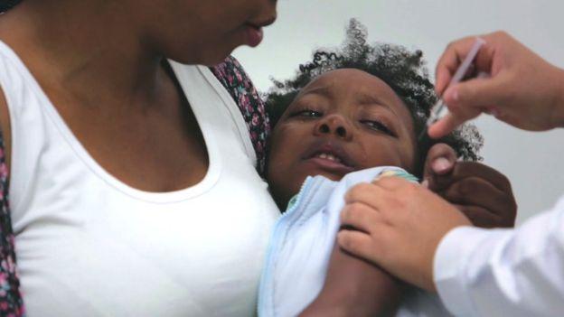 Criança chora no colo da mãe enquanto recebe dose de vacina
