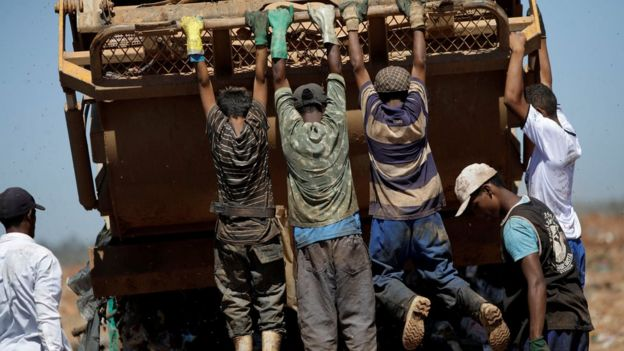 Youths hang from a rubbish lorry at Lixao da Estrutural, Latin America's largest rubbish dump, in Brasilia, Brazil, 19 January 2018