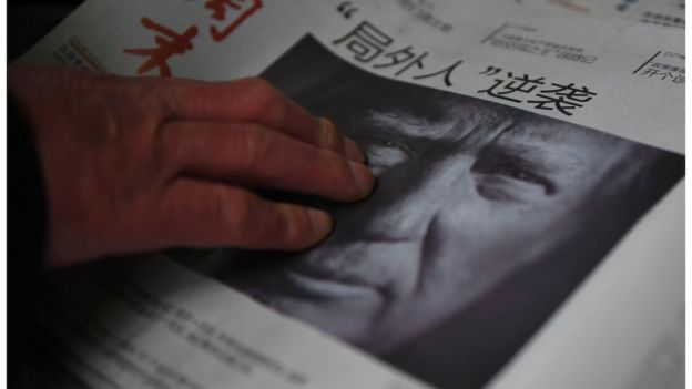 Shows a man buying a newspaper featuring a photo of US President-elect Donald Trump, the day after the US election, at a news stand in Beijing on November 10, 2016. The headline reads