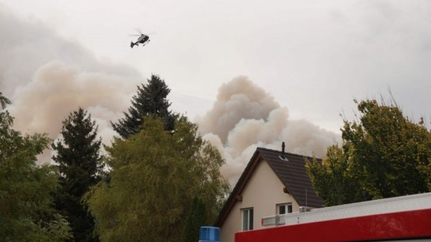 Smoke rises from a forest fire, as a police helicopter flies over a house in a nearby village