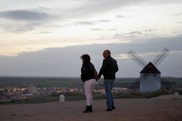Man and woman photographed near a windmill in Mota del Cuervo
