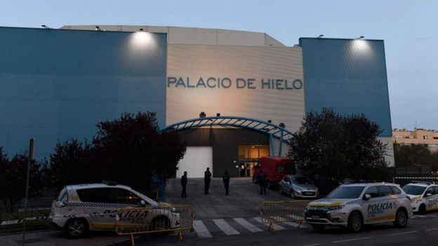 Policemen stand outside the Palacio de Hielo (Ice Palace) shopping mall where an ice rink was turned into a temporary morgue on March 23, 2020 in Madrid to deal with a surge in deaths in the Spanish capital due to the coronavirus