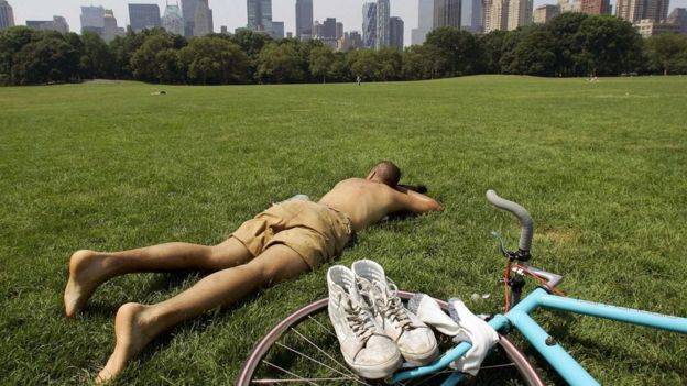 Homem deitado na grama de um parque com bicicleta ao lado