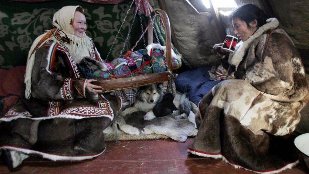Duas mulheres com roupas tradicionais dentro de cabana, com bebê em berço de balanço no meio
