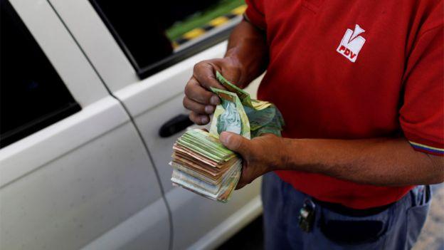 Persona cuenta billetes en una estación de servicio de PDVSA
