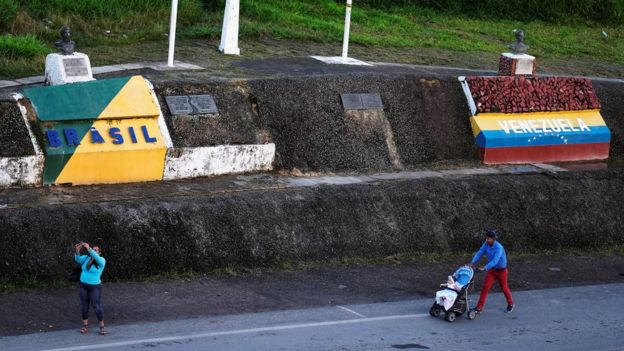 Famílias caminham em estrada em cujas margens estão duas pinturas com dizeres e cores respectivas de cada país: Brasil e Venezuela