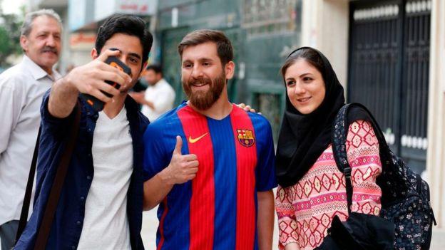 Reza Parastesh tomándose una selfie con desconocidos en la calle.