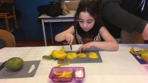 Una niña pica fruta en un centro comunitario de Ámsterdam