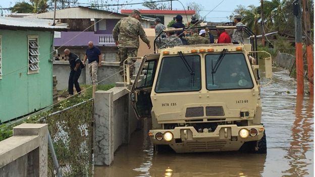 Convoy del ejército sobre calles inundadas.