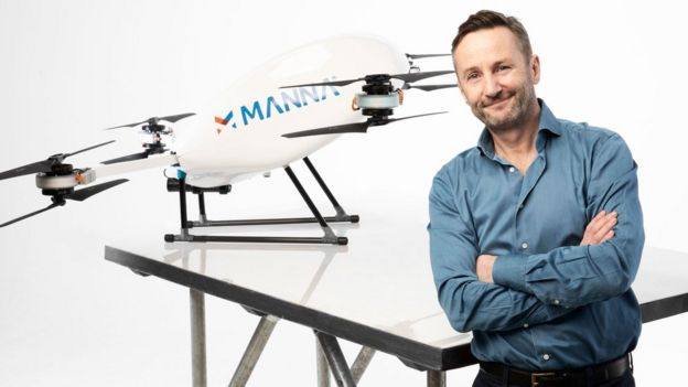 Bobby Healy, wearing a blue shirt and sporting a short beard, stands with his arms crossed in front of his company's drone