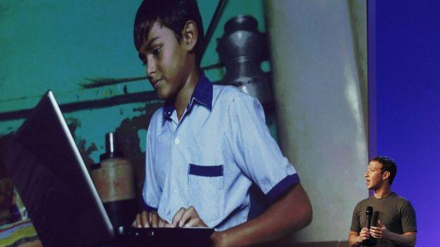 Mark Zuckerberg apresenta projeto em Delhi, no ano de 2014, com foto projetada de menino usando computador ao fundo