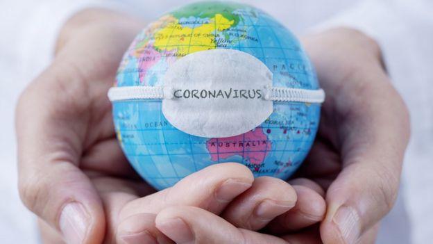 Pequeno globo representando a Terra, com máscara estampando a palavra 'coronavírus'