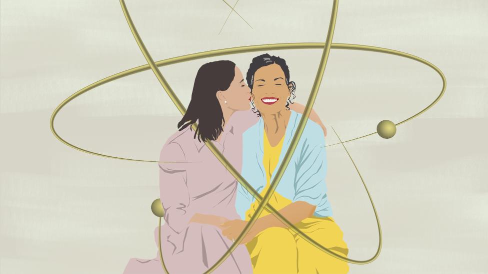 Dos mujeres se abrazan sentadas
