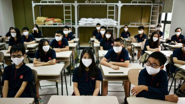 Pelajar di Hanoi memakai masker.