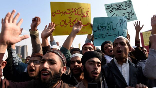 Students of Islamic seminaries hold placards reading in Urdu
