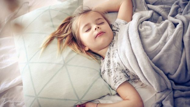 Imagem mostra criança dormindo na cama