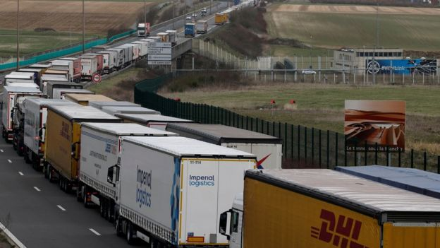 Trucks form a queue on 13 March as French Customs Officers increase controls on transported goods to protest the lack of resources as the Brexit date approaches, in Coquelles, France