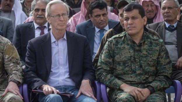 William V. Roebuck (solda) ve SDG komutanı Mazlum Kobani (sağda) ile birlikte Deyr ez Zor'da IŞİD'in Baguz'dan çıkarılmasının ilan edildiği törene katılıyor (23 Mart 2019)