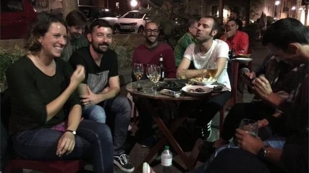 People sit around an outdoor table at a bar in Girona (4 October 2017)