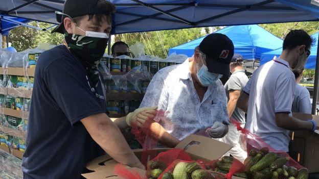 Un grupo de voluntarios preparan cajas de alimentos para donar