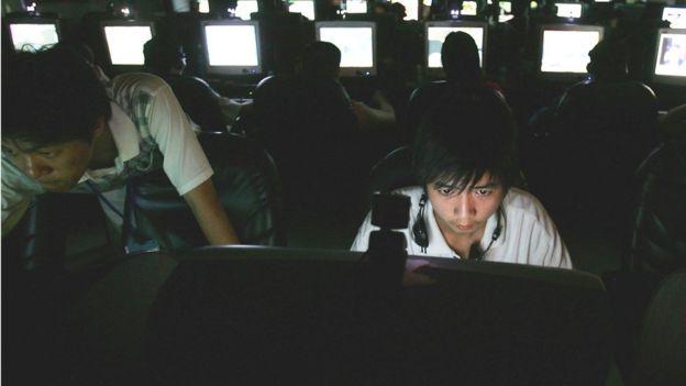 Joven asiático frente a computadoras.