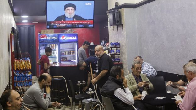 Lebanese men play cards and smoke shishas while listening to a speech by Hezbollah leader Hassan Nasrallah on TV at a coffee shop in Beirut, Lebanon (5 November 2017)