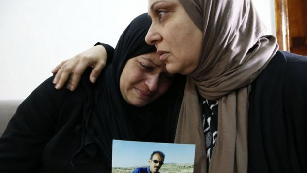 Relatives of Mahmoud Abu Asba mourn him at their home in the occupied West Bank village of Haloul (13 November 2018)