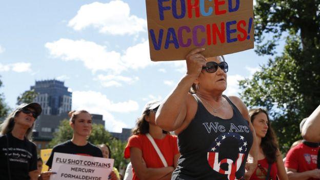 Seorang pengunjuk rasa anti-vaksin mengenakan kaos QAnon di Boston pada hari Minggu