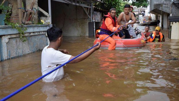 Para petugas penyelamat mengevakuasi warga dari kawasan banjir di Pasar Minggu, jakarta Selatan.