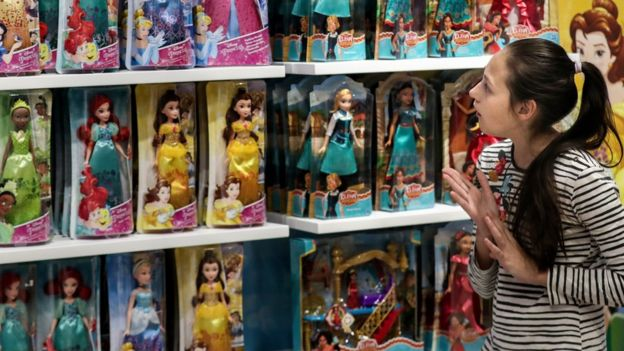 A girl looking at Disney Princess dolls
