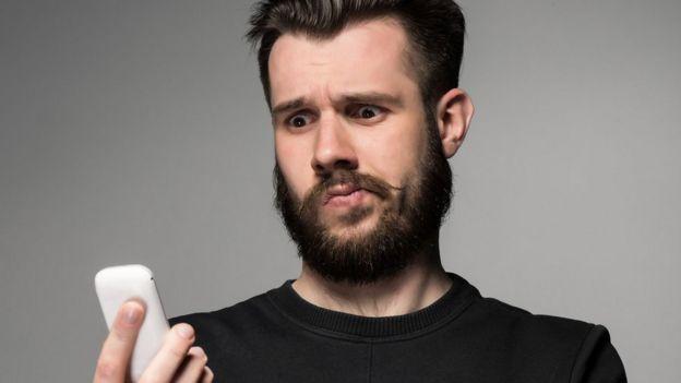 joven mirando con extrañeza un celular
