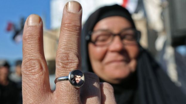 An Iraqi anti-government protester in Baghdad shows a ring bearing a portrait of Moqtada al-Sadr (20 November 2019)