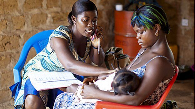 Health worker on the phone while she helps woman and baby