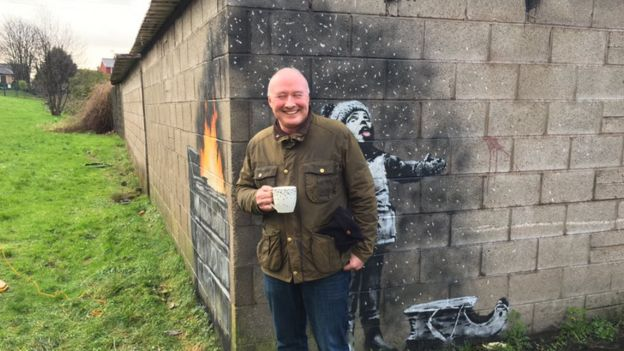 Ian Lewis standing in front of the suspected Banksy