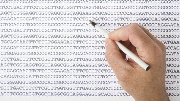 Mão com caneta em cima de papel com letras A G C T indicando blocos de sequências genéticas