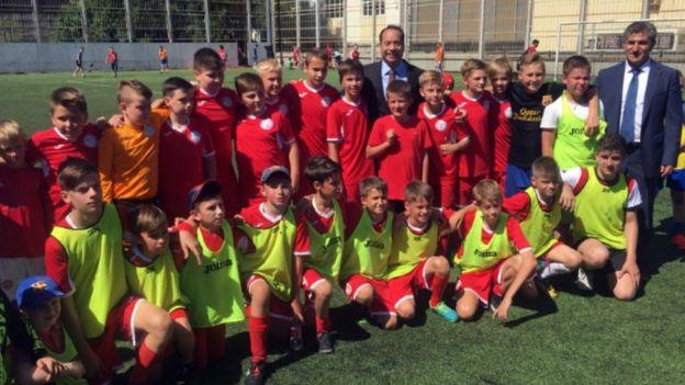 Ministro do Esporte posa com crianças russas uniformizadas em campo de futebol
