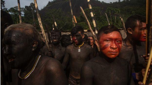 Yanomamis com pintura tradicional de seu povo (corpo escuro e rosto vermelho) em reunião ao ar livre