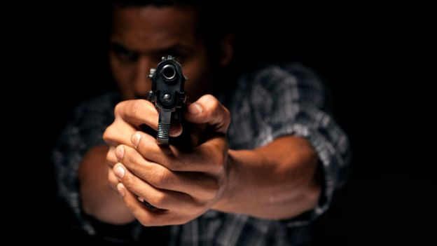 Un hombre disparando un arma