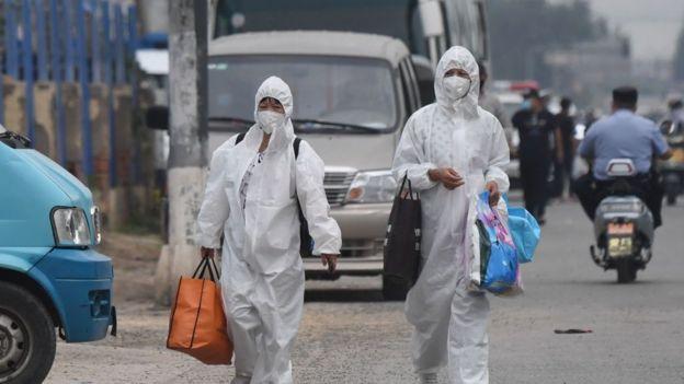 امرأتان ترتديان بدلات واقية أثناء سيرهما في شارع بالقرب من شينفادي المغلق في بكين، في 13 يونيو/حزيران 2020.