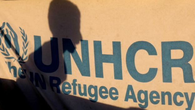 The shadow of a displaced child in Syria on a UNHCR sign in a refugee camp in Ain Issa, July 11, 2017