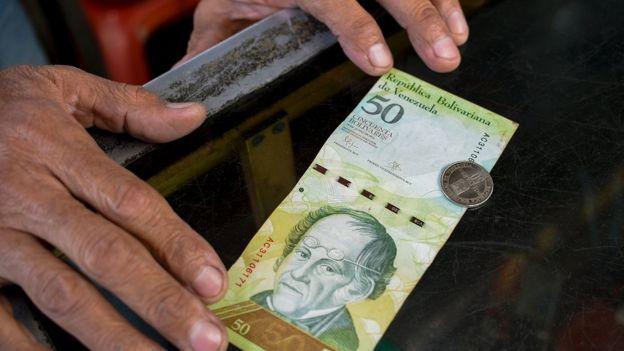 Un hombre compara un billete con una moneda venezolana del mismo valor.