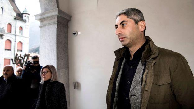 Mr Cosar, clean-shaven and in civilian clothing, arrives at the Federal Criminal Court of Switzerland in Bellinzona