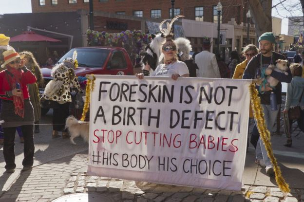 Costumed young woman holds large sign about circumcision saying 'Foreskin is not a birth defect' in the Mardi Gras parade on February 7, 2016 in downtown Asheville, NC