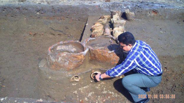 Homem agachado perto de ruínas de fábrica de perfume no Egito