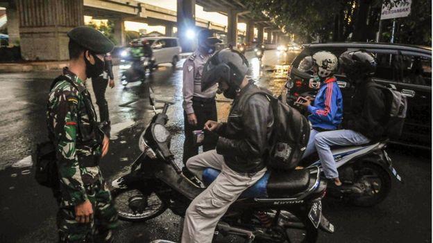 Petugas gabungan TNI /Polri melakukan pengecekan identitas warga yang melakukan mudik lokal di Jakasampurna, Bekasi, Jawa Barat, Senin (25/5/2020).