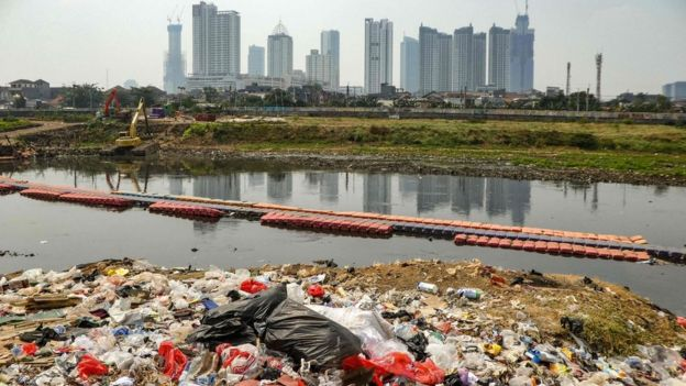 Plastic waste o­n the banks of a river with a view of the Jakarta skyline (file photo - August 2019)