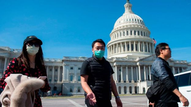 A tour operator, wearing a protective mask, gestures as he leads a tour near the US Capitol in Washington, DC on 9 March, 2020