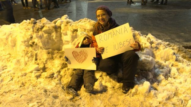 """A mother and her young child carrying signs. One reads: """"Romania, I love you"""""""